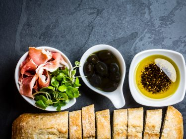 Bread ciabatta, jamon ham serrano paleta iberica, arugula, olive pepper oil, olives, rurosemary and glass of red wine on stone slate black background. Top view copy space